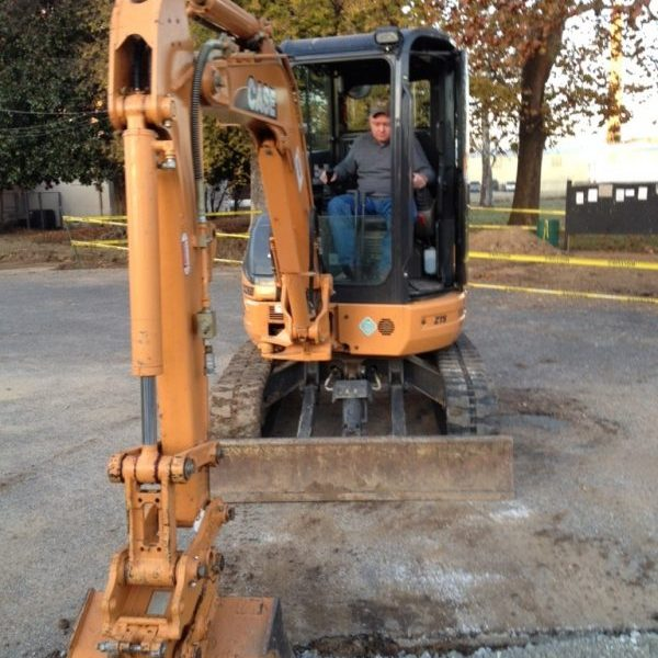 Repairing a hole in a pave street by packing limestone aggregate with an escavator bucket
