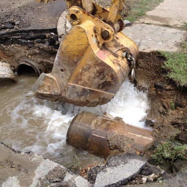 Digging a hole with a backhoe to repair a gushing water line break