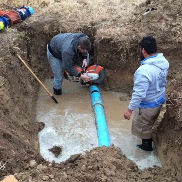 Two men down in a hole, standing in 6 inches of water, cutting and repairing a sewer line break