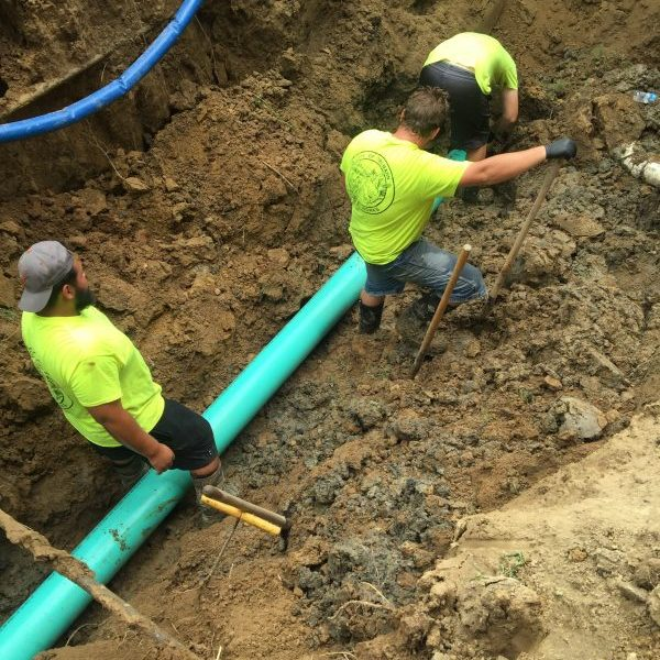 Three public works employees down in a large trench installing a new 8 inch sewer line