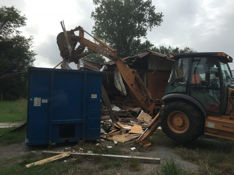 Demolition of a condemned structure and placing the materials in a dumpster with a backhoe.