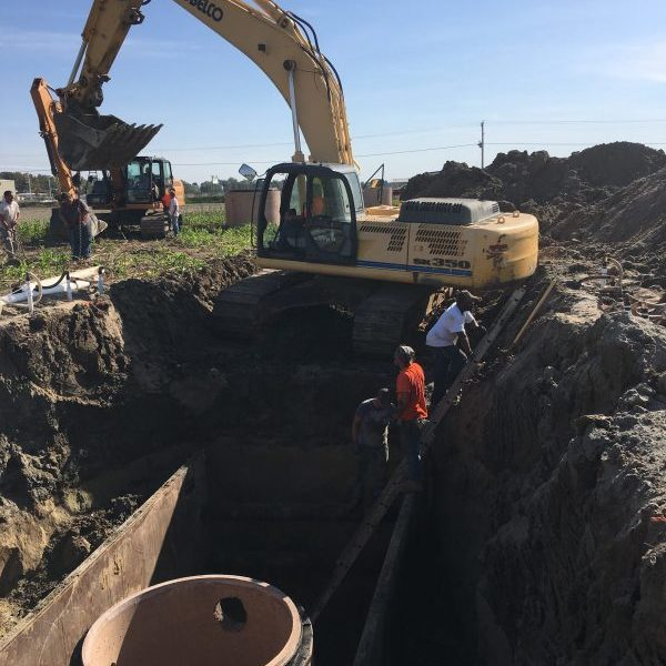 Public works employees installing a new access hole with an escavator.