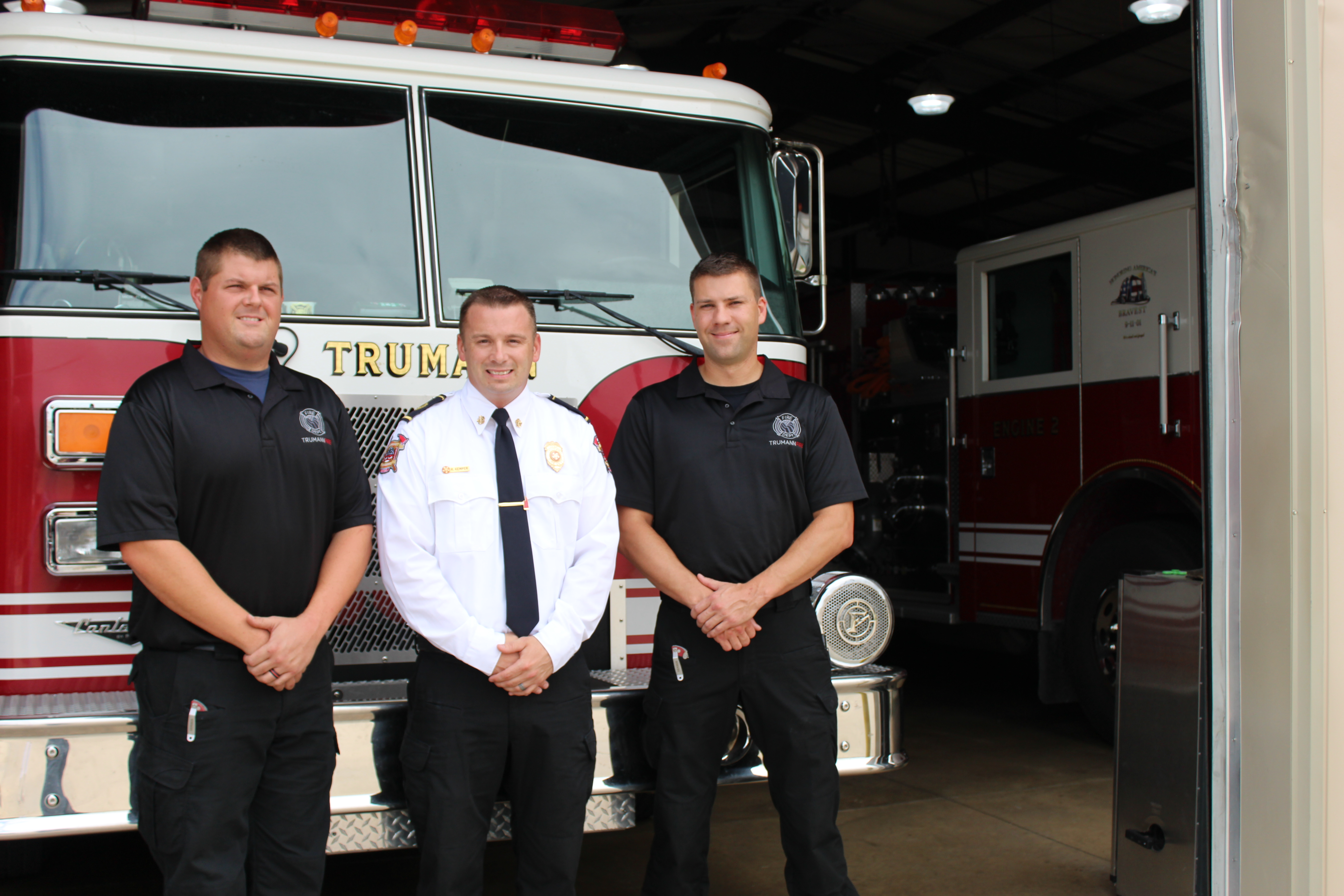 Picture of three Trumann firemen posing in front of the pumper truck